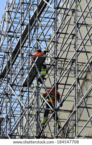 workers assemble metal construction on blue sky background - stock photo