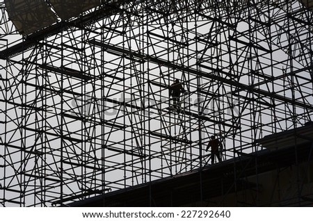 workers assemble metal construction on blue sky background