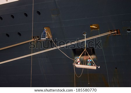 Workers at a hull of big ship - stock photo