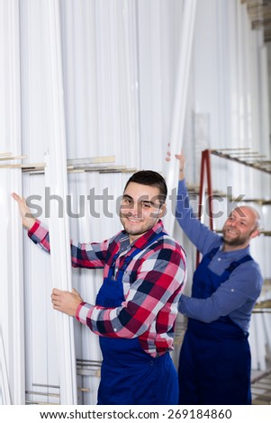 Workers at a window production factory searching for specific PVC profiles - stock photo
