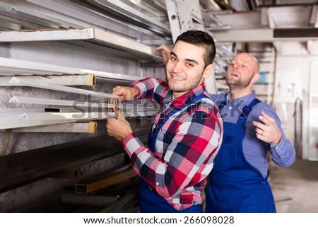 Workers at a workshop producing pvc windows are taking an aluminum window frame from a rack - stock photo