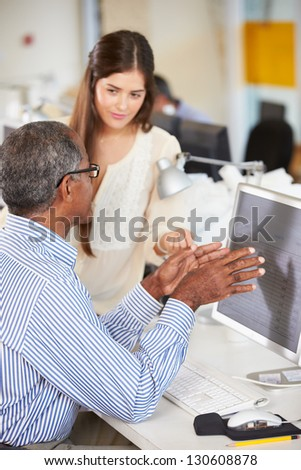 Workers At Desks In Busy Creative Office - stock photo