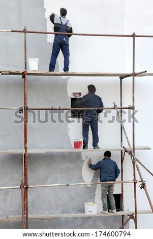 Workers at scaffolding spreading stucco over mortar and styrofoam wall insulation with trowel - stock photo