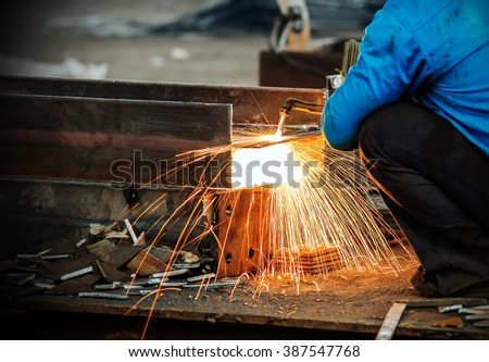 Workers at the construction site using a metal cutting torch - stock photo