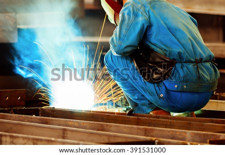 Workers at work, ongoing welding operation. - stock photo