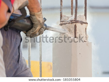 Workers break reinforced concrete with jackhammer at a construction site
