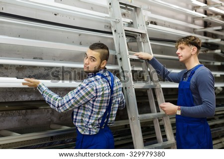 workers choosing window profiles at factory - stock photo