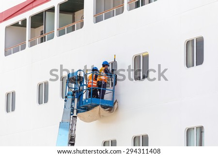 Workers cleaning windows on cruise ship in port - stock photo