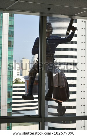 workers cleaning windows service on high rise building - stock photo