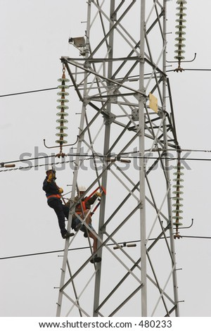 Workers climbing on power pylon