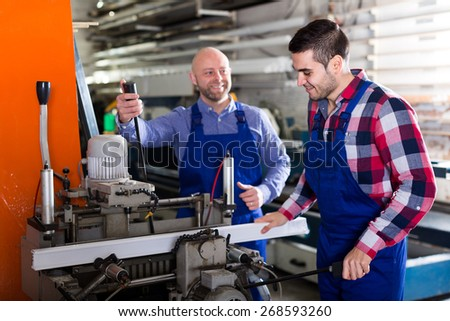 Workers cutting aluminum profiles on a window production facility - stock photo