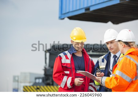 Workers discussing over clipboard in shipping yard - stock photo