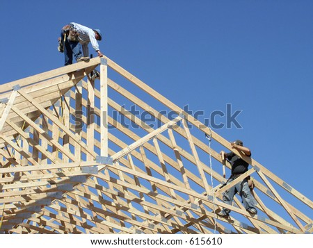 workers framing roof of a building