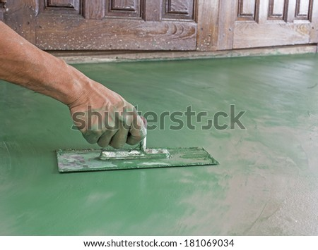 Workers  hand plastering color combination  a floor  with trowel. Construction worker. Masonry tool. Construction industry. Selective focus.  - stock photo