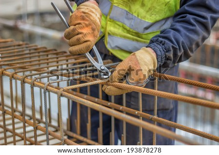 workers hands using steel wire and pincers to secure rebar before concrete is poured over it. Selective focus on center portion of image. - stock photo