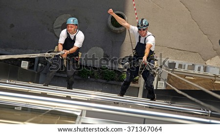 Workers hanging on climbing ropes, showing raised fist sign. Glass Cleaning Services. Industrial Climbers Hanging on Ropes. Window and Facade Cleaning.