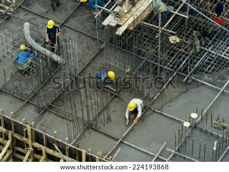 Workers in construction site, elevated view - stock photo