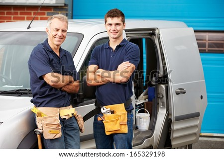 Workers In Family Business Standing Next To Van - stock photo