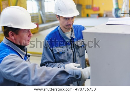 Workers in overalls and helmets in the premises of the factory