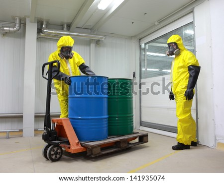 Workers in protective uniform,mask,gloves and boots working with barrels of chemicals on forklift - stock photo