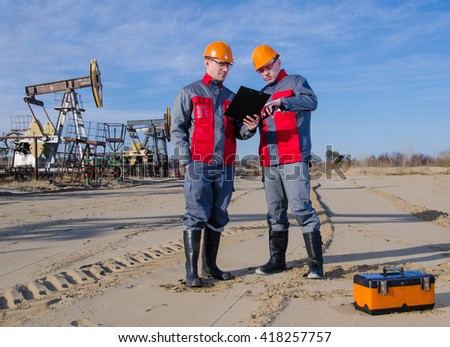 Workers in the oilfield, one holding radio in his hand. Pump jack and wellhead background. Toolbox foreground. Oil and gas concept.