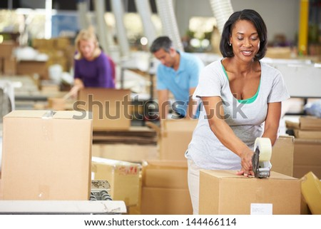 Workers In Warehouse Preparing Goods For Dispatch - stock photo