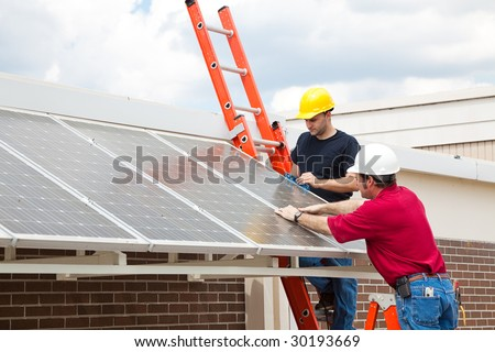 Workers install energy efficient solar panels on the roof of a building. - stock photo