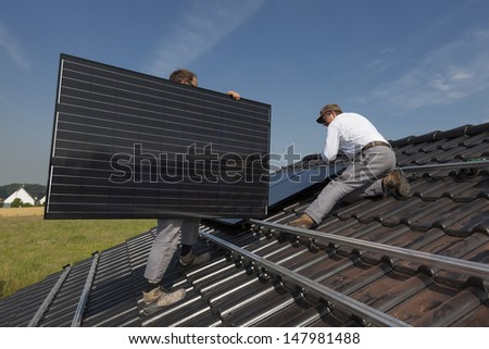 workers installing alternative energy photovoltaic solar panels on the roof of a single family house