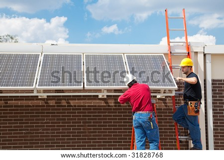 Workers installing solar panels on the side of a building.  Wide angle view with room for text. - stock photo