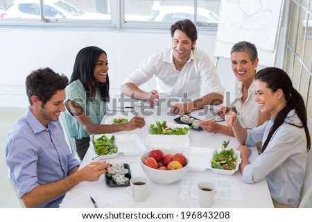 Workers laughing while enjoying lunch break in the office - stock photo