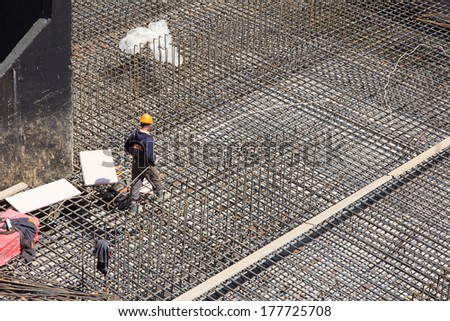 workers make metal reinforcement for the concrete foundation - stock photo
