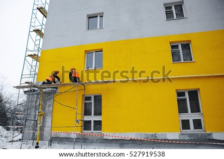 Workers make repairs on the facade of a residential building