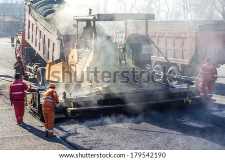 Workers making asphalt with shovels at road construction - stock photo