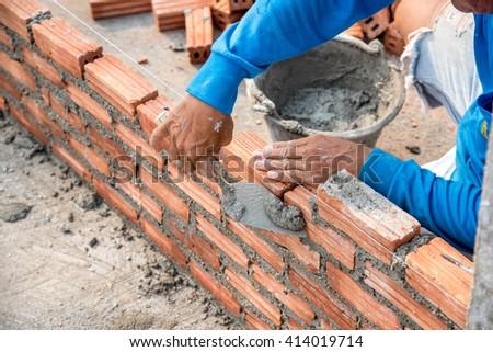 Workers masonry Clay brick to wall - stock photo