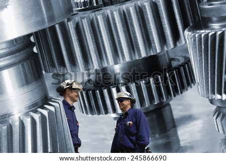 workers, mechanics and large cogwheels machinery, steel industrial. - stock photo