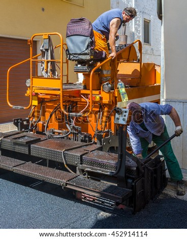 workers on a paver machine control the drafting of a new layer of asphalt for maintenance of city streets