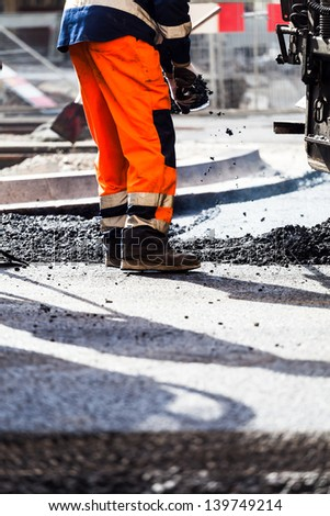 Workers on a road construction, industry and teamwork . Man working on a new asphalt street. - stock photo