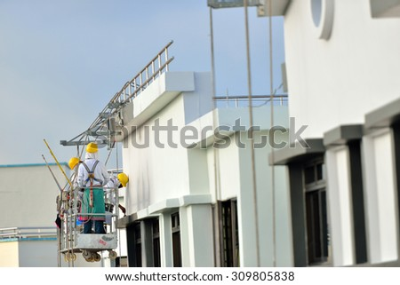 Workers painting the exterior walls in public housing block - stock photo