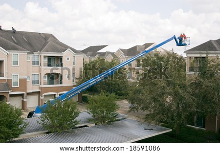 Workers placing temporary coverings on roofs of an apartment complex damaged during a hurricane.