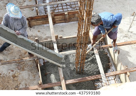 Workers pour ready mix concrete from mix concrete vehicle to a footing of a column, reinforcement with steel. Lay on ground above plastic cover sheet. With square formwork.   - stock photo