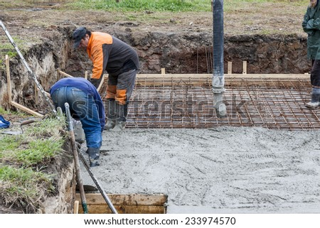 Workers pouring concrete mix into reinforced structure at the building site. - stock photo