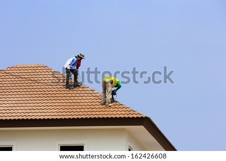 Workers   repair  concrete  roof  tile  - stock photo