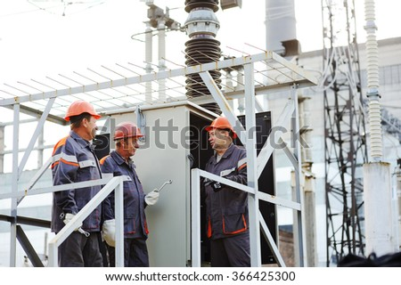 workers repairing a transformer at the power station. - stock photo