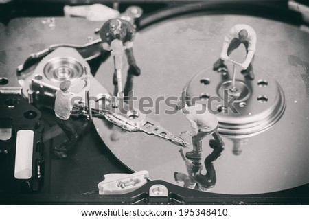 Workers repairing hard disc. Macro photo with retro style effect - stock photo