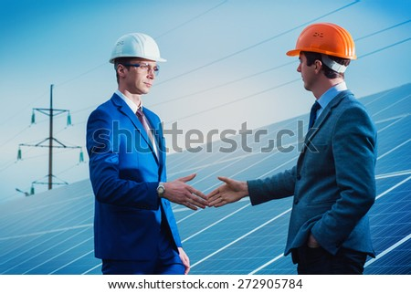 Workers shaking hands on a background of solar panels on solar power plant.