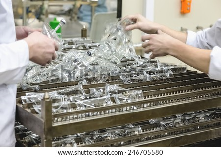 Workers sorts production on pharmaceutical industry manufacture or chemical plant - stock photo