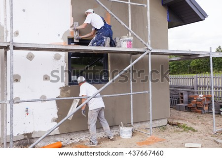 Workers spreading mortar over styrofoam insulation and mesh with trowel - stock photo