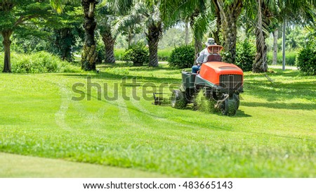 Workers use mower working on the golf course