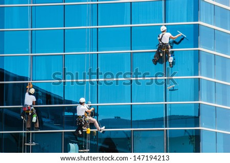 workers washing windows of the modern skyscraper building