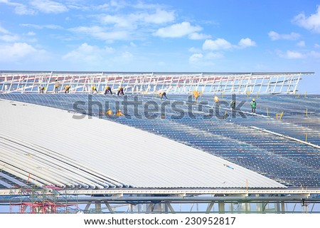 Workers wear safety equipment to Working at Heights on a high roof, large plants. Built with a steel rod and sheet aluminum is strong, modern design. under blue sky and cloud space.